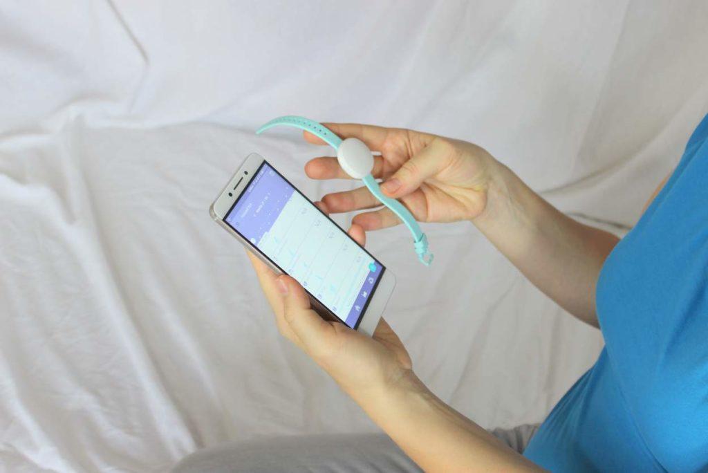 Ava Armband und Zyklusbericht über Smartphone