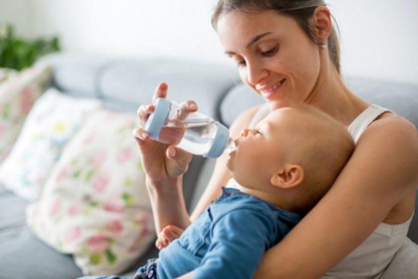 Mutter füttert Baby mit Wasser in der Babyflasche