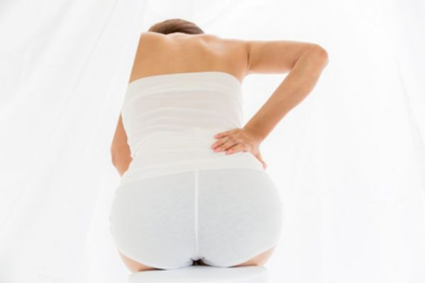 Schwangere Frau mit Schmerzen im Po und Rücken