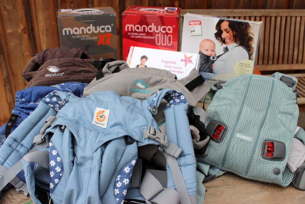 Getestete Babytragen samt Verpackung liegen auf dem Tisch