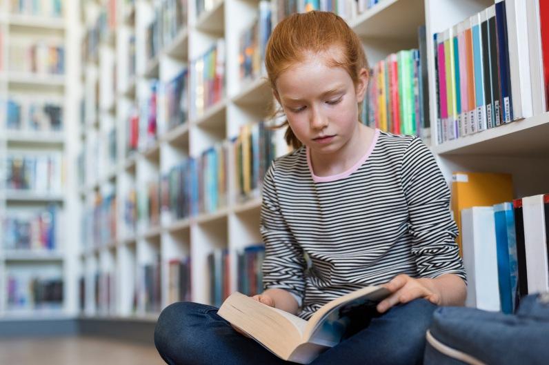 Hochbegabtes Kind mit Buch in Bibliothek