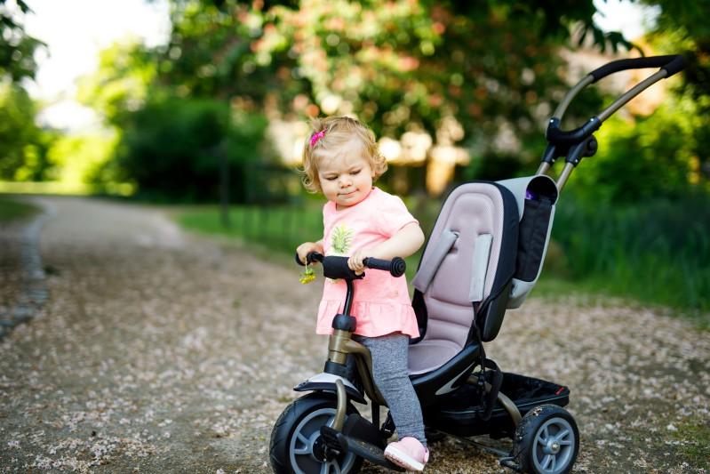 Kleinkind sitzt auf modernem Dreirad