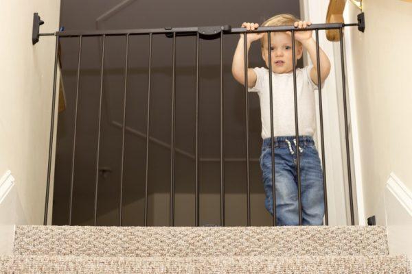 Kleinkind steht vor Treppenschutzgitter