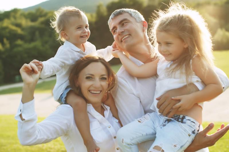 glueckliche-familie-bei-sonnenschein-auf-wiese