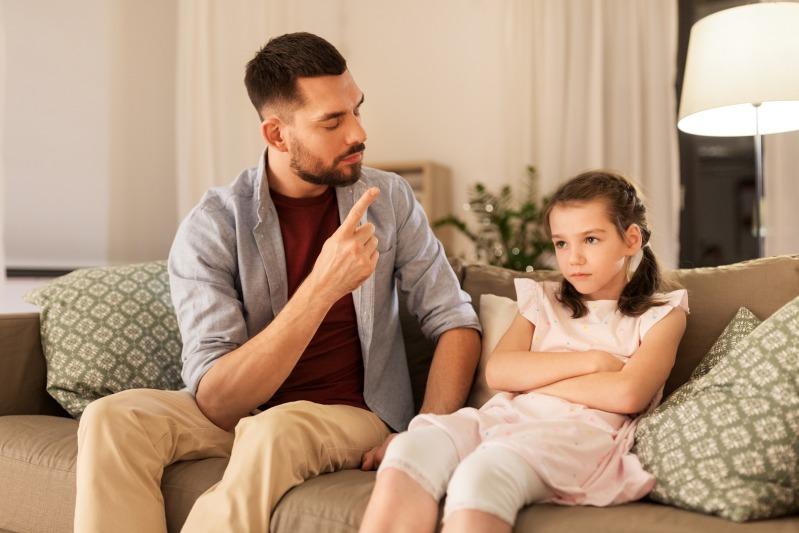 Vater mit autoritärem Erziehungsstil schimpft mit Tochter