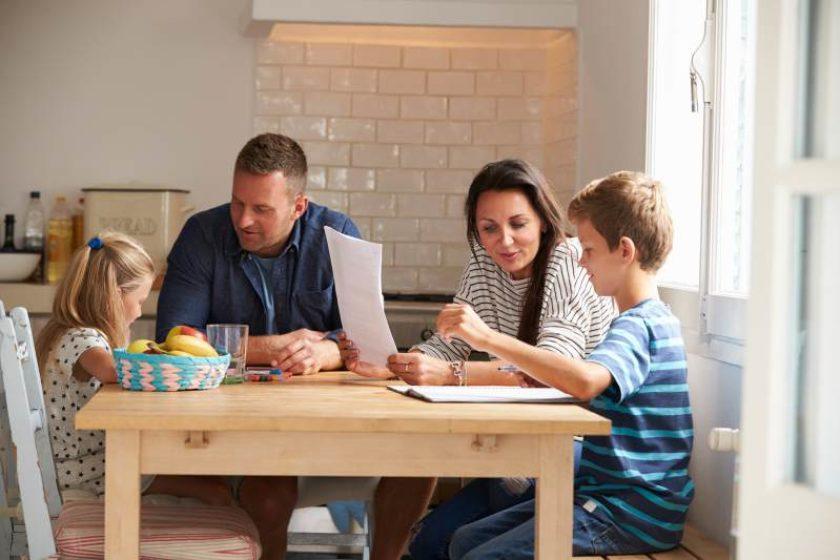Eltern sitzen mit Kinder am Essentisch und helfen bei den Hausaufgaben