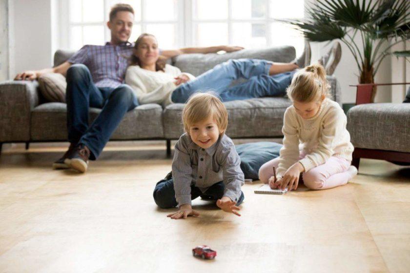 Kinder spielen im Wohnzimmer auf Fussboden und Eltern sitzen auf der Couch