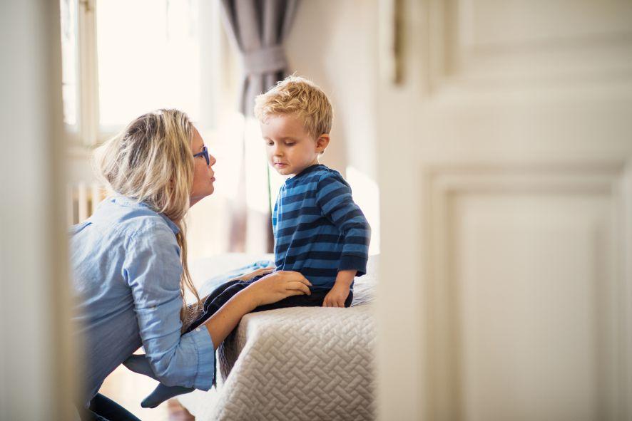 Mutter erzieht Sohn mit autoritativer Erziehungs und spricht mit ihm im Schlafzimmer