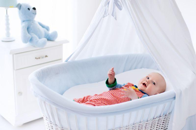 Baby liegt im Babyzimmer mit Stubenwagen