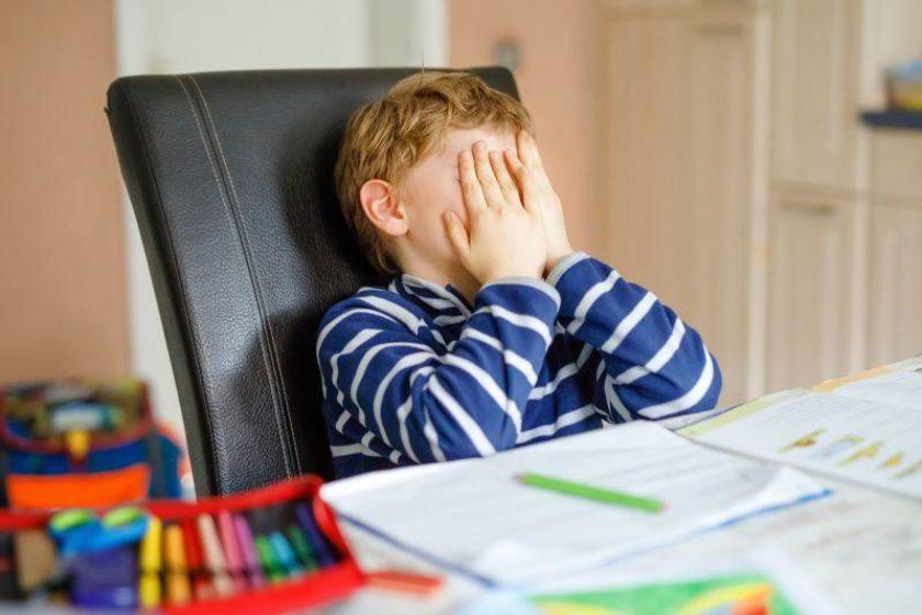 Junge sitzt frustriert und unglücklich im Kinderzimmer am Schreibtisch vor seinen Hausaufgaben