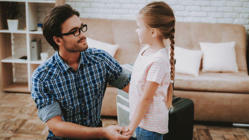 Vater und Tochter stehen in Wohnung vor braunem Sofa