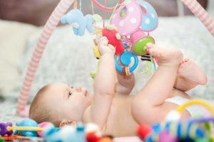6-monate-altes-baby-spielt-unter-spielebogen
